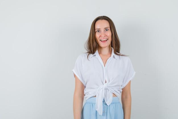 Młoda dama uśmiecha się w bluzkę i spódnicę i wygląda radośnie