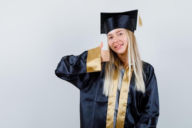 Młoda dama w akademickiej sukience pokazująca kciuk w górę i wyglądająca na szczęśliwą