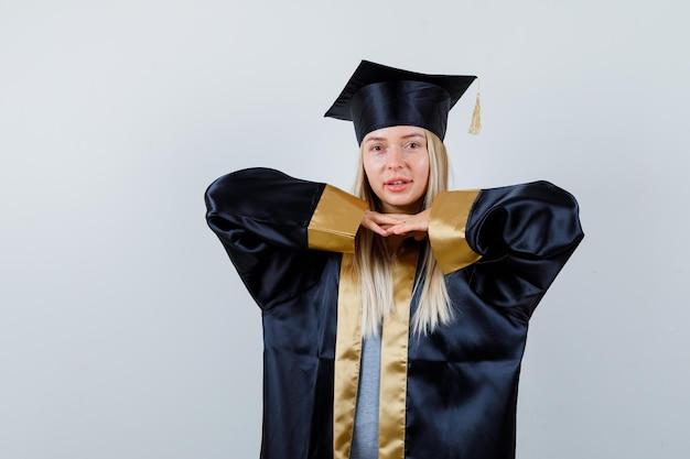 Młoda dama w akademickiej sukience trzymająca się za ręce pod brodą i wyglądająca wspaniale