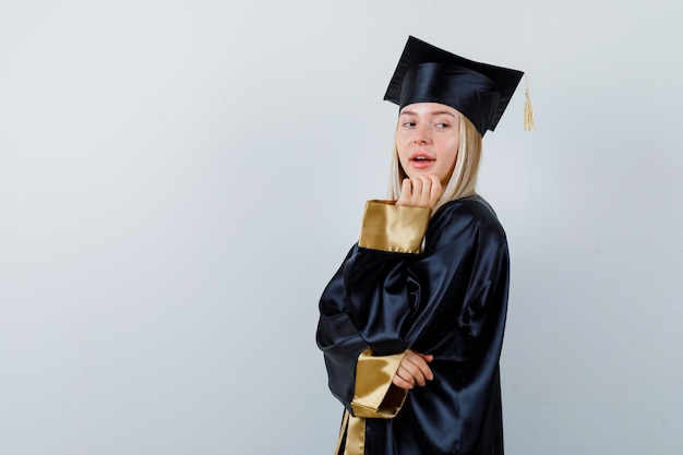 Młoda dama w akademickim stroju pozuje, stojąc i wygląda wspaniale