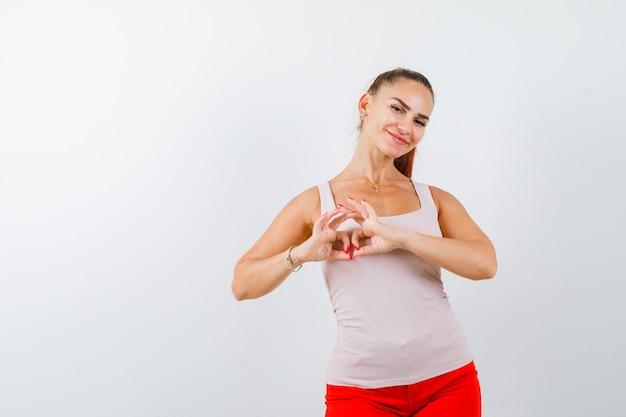 Młoda dama w beżowym podkoszulku bez rękawów pokazuje gest serca i wygląda ładnie