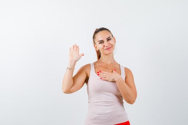 Młoda dama w beżowym podkoszulku trzyma rękę na piersi, pokazując dłoń i wygląda na zadowoloną, widok z przodu.