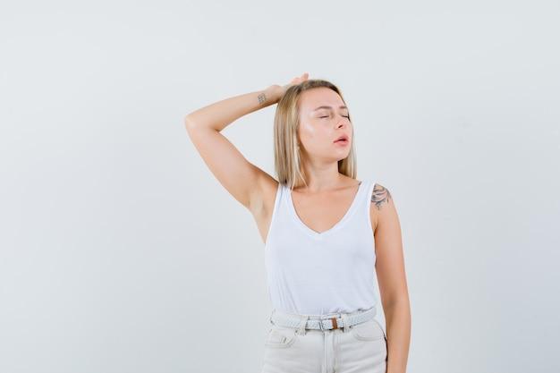 Młoda dama w białej bluzce cierpi na bóle głowy i wygląda na bolesną