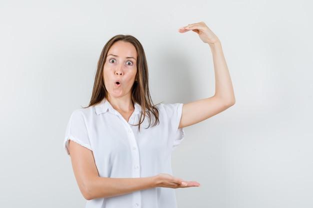 Młoda dama w białej bluzce pokazująca duży znak rozmiaru i wyglądająca na zaskoczoną