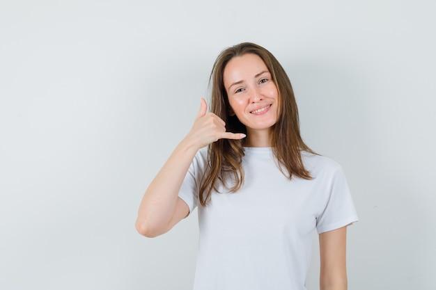 Młoda dama w białej koszulce pokazuje gest telefonu i szuka pomocnego