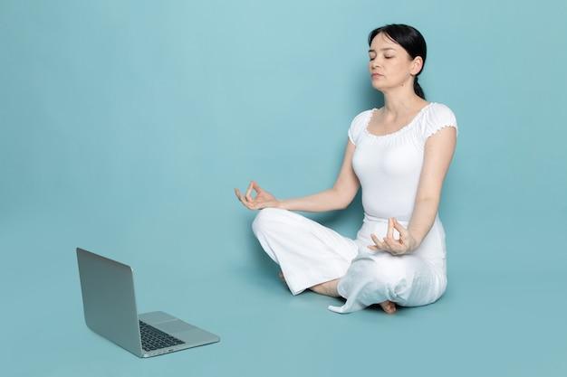 Młoda dama w białej koszuli białe spodnie w youga stanowią patrząc za pomocą szarego laptopa na niebiesko