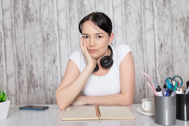 Młoda dama w białej koszuli pokazując emocje rękami w czarnych słuchawkach na szarej ścianie