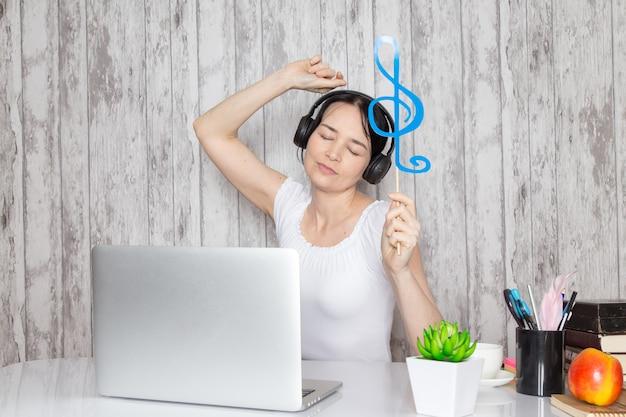 Młoda dama w białej koszuli trzymająca niebieską nutę słuchająca muzyki przez czarne słuchawki na stole wraz z długopisami z zielonymi roślinami na szaro
