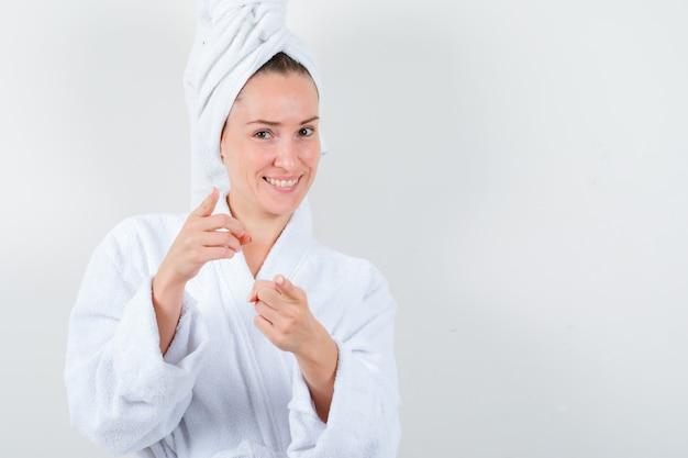 Młoda dama w białym szlafroku, ręcznik, wskazując na aparat i patrząc radośnie, widok z przodu.