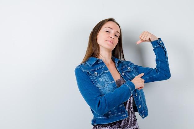 Młoda dama w bluzce, dżinsowej kurtce, wskazując na mięśnie ramion i wyglądająca pewnie, widok z przodu.