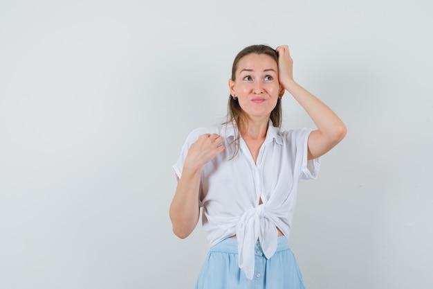 Młoda dama w bluzce i spódnicy drapiąca się po głowie i patrząc niepewnie