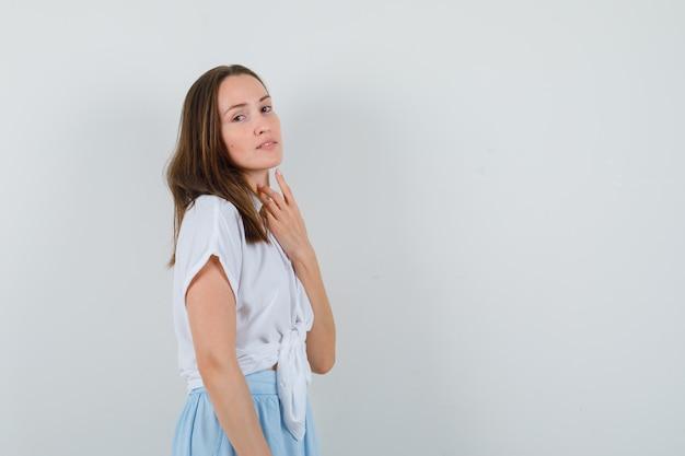 Młoda dama w bluzce i spódnicy, patrząc na bok, pozując i wyglądając atrakcyjnie wolnego miejsca na tekst