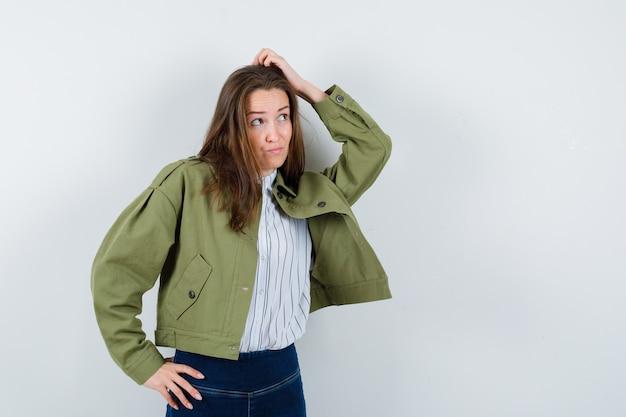 Młoda dama w bluzce, kurtce drapiącej się po głowie i patrząca niezdecydowanie