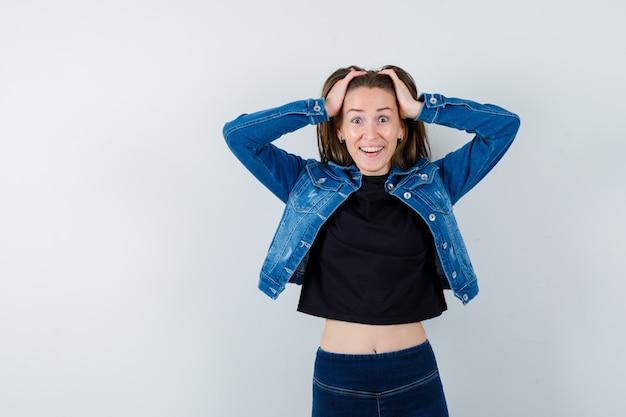 Młoda dama w bluzce, kurtce, dżinsach, trzymając głowę rękami i patrząc szczęśliwy, widok z przodu.