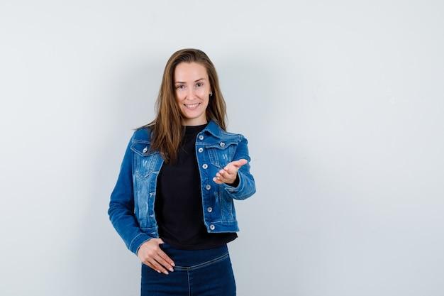 Młoda dama w bluzce, kurtce, dżinsach wyciąga rękę, żeby coś pokazać i wygląda pewnie