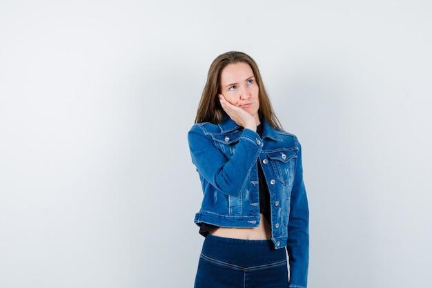 Młoda dama w bluzce opierając policzek na dłoni i patrząc zamyślony, widok z przodu.