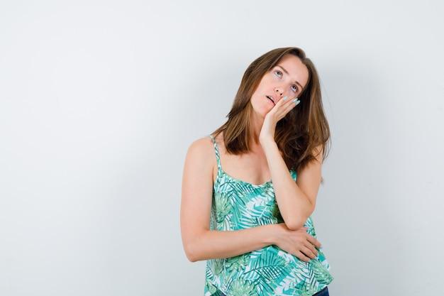 Młoda dama w bluzce opierając policzek pod ręką, patrząc w górę i wyglądając na wyczerpaną, widok z przodu.