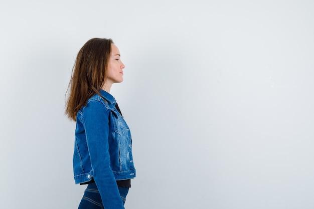 Młoda dama w bluzce patrzy na siebie i wygląda na spokojną.