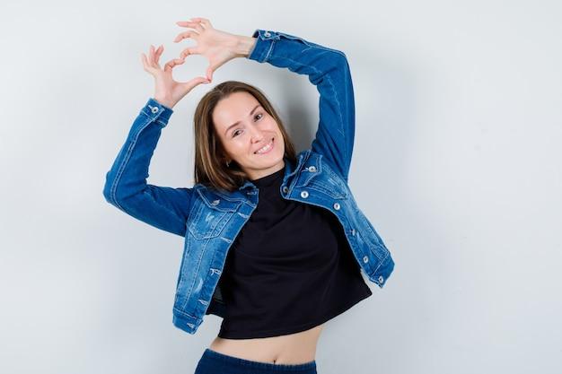 Młoda dama w bluzce pokazując gest serca i patrząc wesoły, widok z przodu.