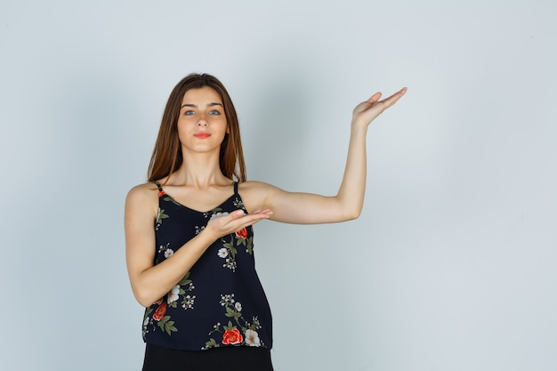 Młoda dama w bluzce, spódnica pokazująca powitalny gest i wyglądająca pewnie, widok z przodu.