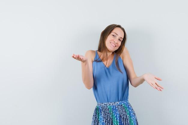 Młoda dama w bluzce, spódnicy pokazuje bezradny gest i wygląda rozbawiony, widok z przodu. miejsce na tekst