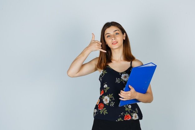 Młoda dama w bluzce, spódnicy trzymając folder, pokazując gest telefonu i patrząc pomocną, widok z przodu.