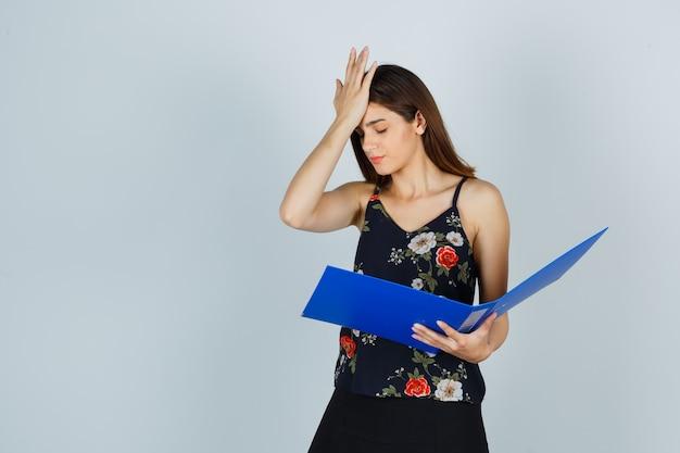 Młoda dama w bluzce, spódnicy trzymając folder trzymając rękę na czole i patrząc zdenerwowany, widok z przodu.