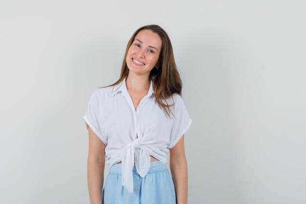Młoda dama w bluzce, uśmiechnięta spódnica stojąc z przodu i wyglądająca uroczo