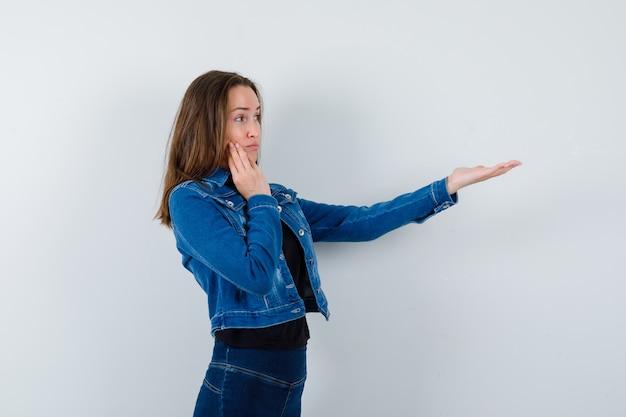 Młoda dama w bluzce wyciąga rękę, żeby coś pokazać i wygląda na skupioną.