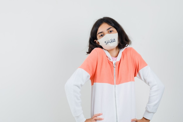Młoda dama w bluzie z kapturem, z maską unoszącą ramiona i leniwym wyglądem
