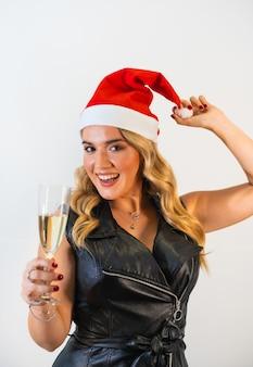 Młoda dama w czapce mikołaja i stylowej czarnej sukience pozuje przy lampce szampana