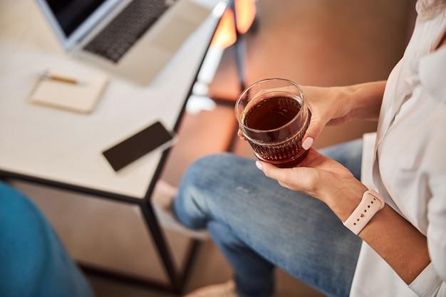 Młoda dama w czasie przerwy przy szklance herbaty lub kawy w biurze