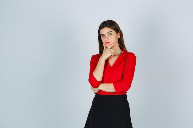 Młoda dama w czerwonej bluzce, czarnej spódnicy, opierając brodę na dłoni