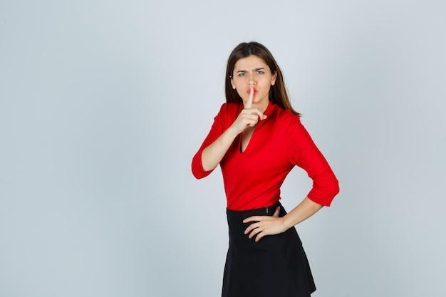Młoda dama w czerwonej bluzce, czarnej spódnicy pokazuje gest ciszy