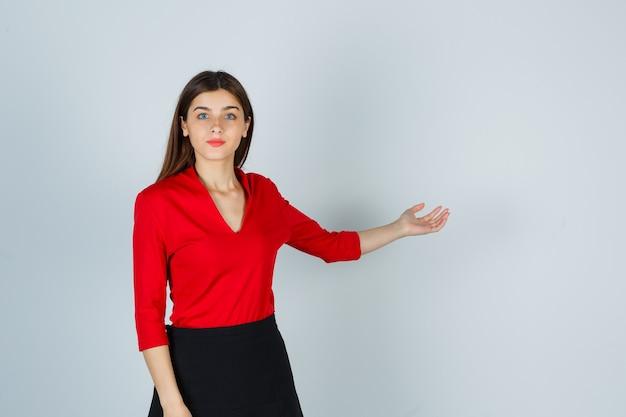 Młoda dama w czerwonej bluzce, czarnej spódnicy wyciągającej rękę jak coś trzymającego