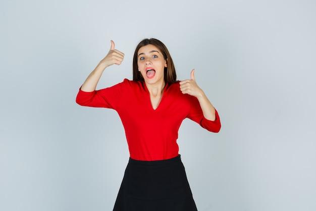 Młoda dama w czerwonej bluzce, czarnej spódnicy z podwójnymi kciukami do góry i wyglądającą wesoło