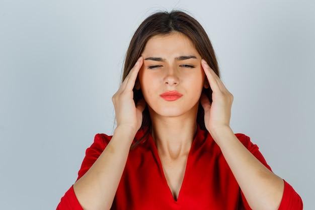 Młoda dama w czerwonej bluzce ociera skronie i wygląda na wyczerpaną