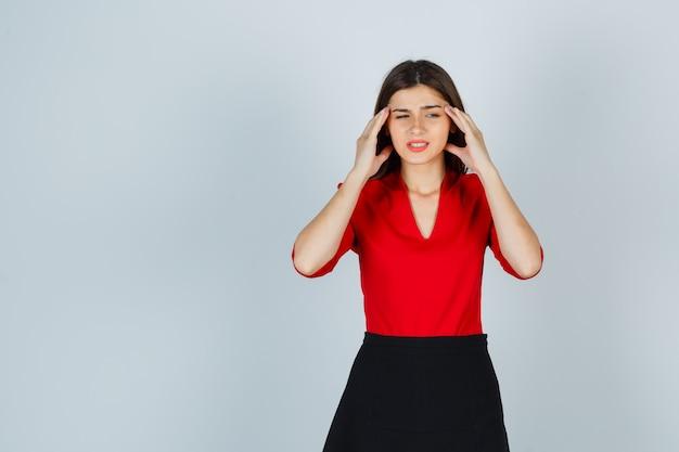 Młoda dama w czerwonej bluzce, spódnicy cierpiącej na ból głowy i wyglądającej na bolesną