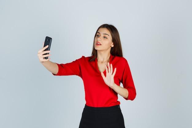 Młoda dama w czerwonej bluzce, spódnicy, nawiązywanie połączenia wideo, machając ręką