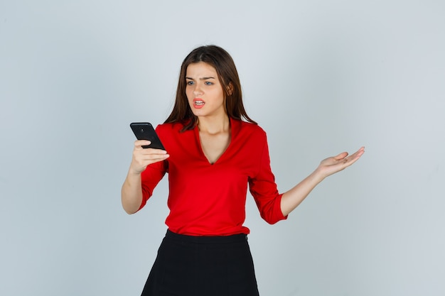 Młoda dama w czerwonej bluzce, spódnicy patrząc na telefon komórkowy