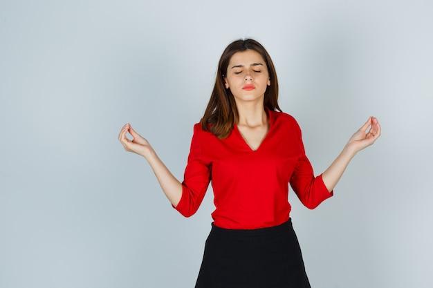 Młoda dama w czerwonej bluzce, spódnicy pokazuje gest medytacji i wygląda spokojnie