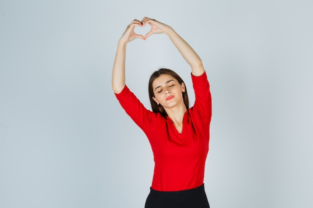 Młoda dama w czerwonej bluzce, spódnicy pokazuje gest serca i ładnie wygląda