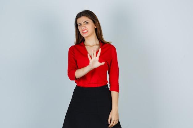 Młoda dama w czerwonej bluzce, spódnicy pokazuje gest stop i wygląda na zniesmaczoną