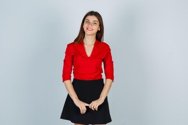 Młoda dama w czerwonej bluzce, spódnicy pozowanie, patrząc na kamery i patrząc wesoło