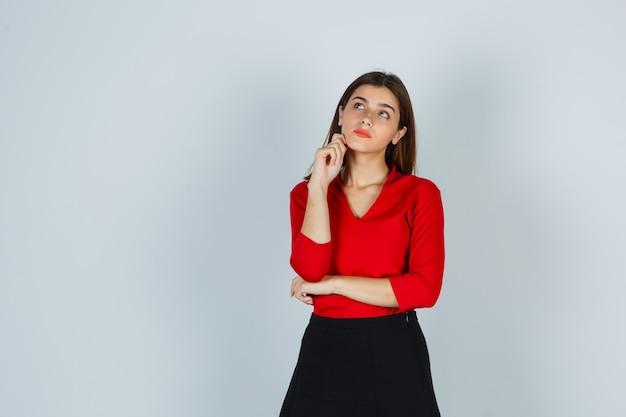 Młoda dama w czerwonej bluzce, spódnicy stojącej w myśleniu poza i patrząc zamyślony