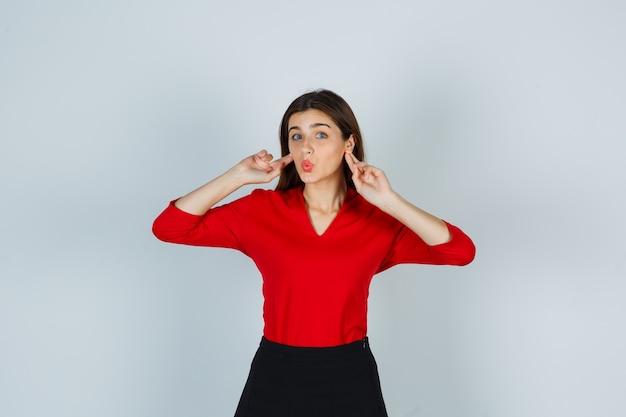 Młoda dama w czerwonej bluzce, spódnicy, trzymając palce za uszami i wyglądając śmiesznie