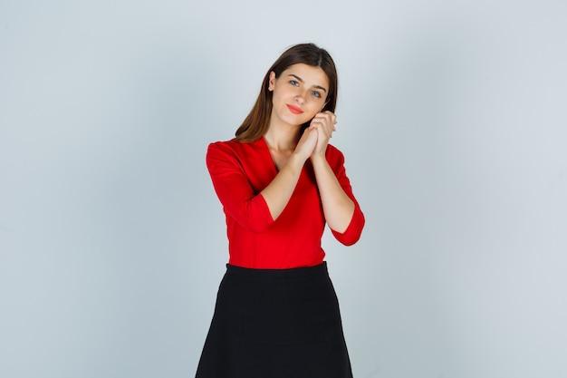 Młoda dama w czerwonej bluzce, spódnicy wsparta na rękach jak poduszka i wyglądająca na zadowoloną