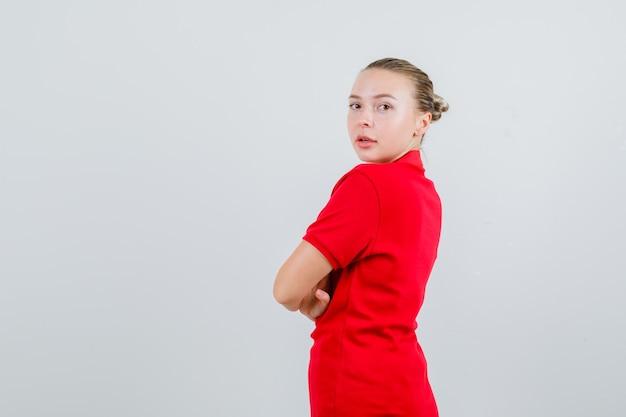 Młoda dama w czerwonej koszulce patrząc na kamery ze skrzyżowanymi rękami.