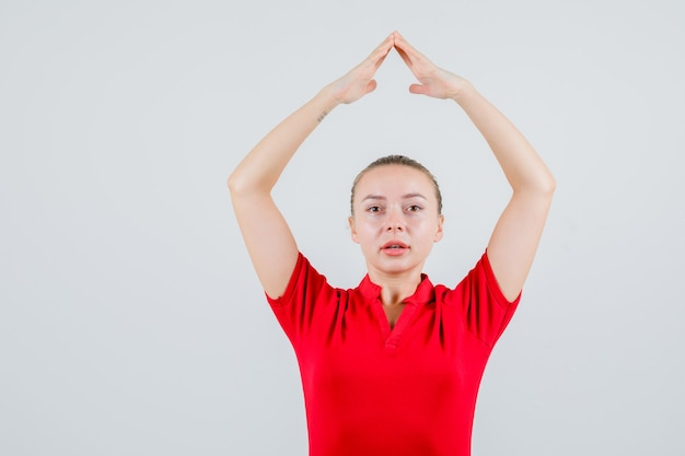 Młoda dama w czerwonej koszulce robi gest na dach domu nad głową