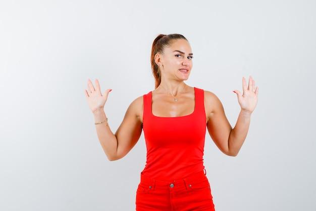 Młoda dama w czerwonym podkoszulku, czerwonych spodniach pokazujących dłonie, patrząc na kamerę i patrząc wesoło, widok z przodu.